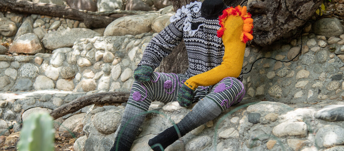 life-sized plastic mannequin vibrantly covered with deconstructed knit sweaters