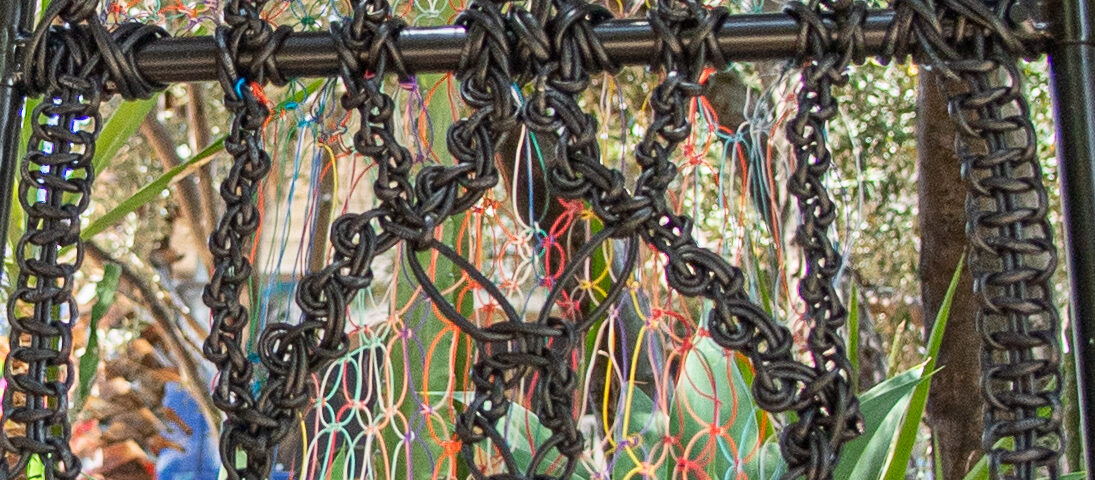 strands of internet cable linked together to create a ladder-like form that climbs out into a colorful opening